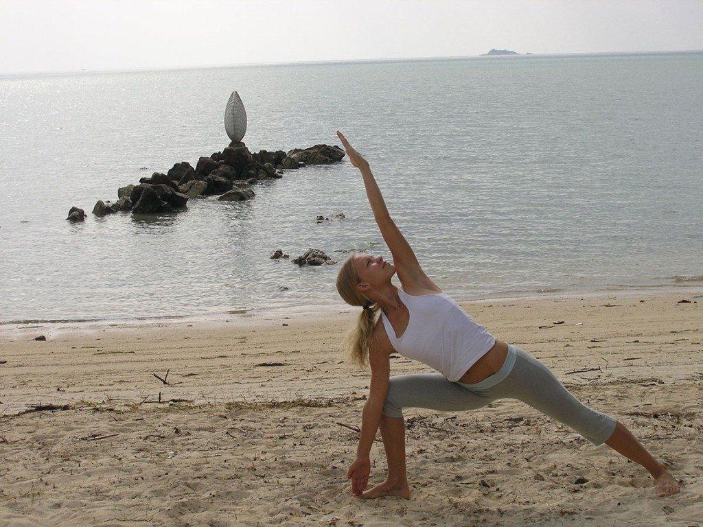 Yoga girl posing at the beach