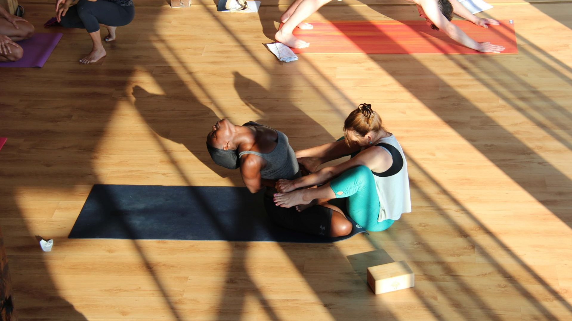 Yoga teacher Valerie giving instructions while a trainee is posing in Bulgaria